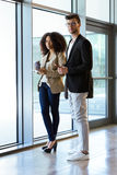 Two young business partners looking at camera in a hallway of they company. Royalty Free Stock Photography