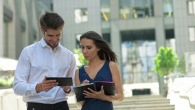 Two young business partners working on the street.Business partners discussing documents and ideas, standing in front of. Business partners discussing documents stock video footage