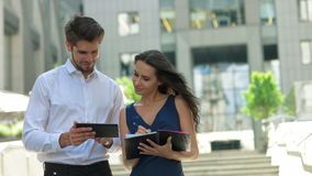 Two young business partners working on the street.Business partners discussing documents and ideas, standing in front of Royalty Free Stock Image