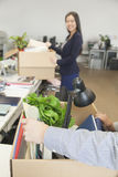 Two young business people carrying boxes with office items Stock Photography