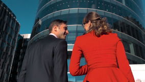 Two young business people discussing. Slow motion. Two young business people discussing outdoor with glass building bg. Male and female, man and woman. Smile stock footage