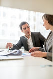 Two Young Business People Discussing at the Table Stock Image