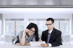 Business people discuss with tablet computer. Two young business people discussing with a tablet computer on desk in the office room Stock Image