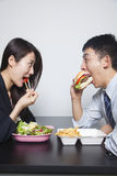 Two young business people eating a meal Royalty Free Stock Images