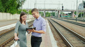 Two young business people on the platform are waiting for their train. They use a tablet, stand near the railway. Two business people on the platform are waiting stock footage