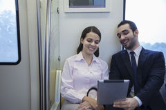 Two young business people sitting and looking at a digital tablet on the subway Stock Photography