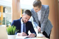 Two young business people using laptop in office while collaborating on startup project. Two young business people using laptop in office while collaborating on royalty free stock photo