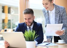 Two young business people using laptop in office while collaborating on startup project. Two young business people using laptop in office while collaborating on royalty free stock image