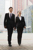 Two young business people walking outdoors, Beijing, China Royalty Free Stock Images
