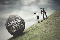 Workers pull a stone with Interest Rates text. Two young business team pull up a stone on the hill with Interest Rates text royalty free stock images