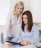 Two young business woman in the office looking at a document. Royalty Free Stock Images