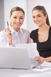 Two young business woman or office workers discussing paperwork. Royalty Free Stock Photo