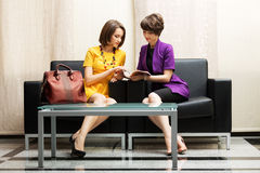 Two young fashion woman reading a magazine Royalty Free Stock Image