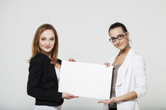Two young business women. With billboard Stock Photo