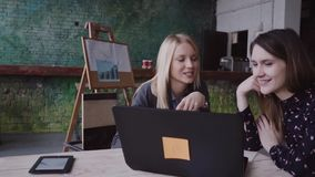 Two young business women blond and brunette meeting in modern office discussing start-up ideas. Brainstorming of colleague, sharing the news stock footage