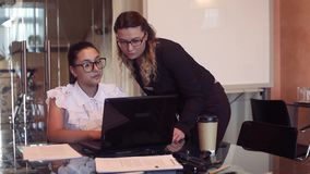 Two young business women discuss a business project in an office using a computer. Two beautiful young business women discuss a business project in the office stock footage
