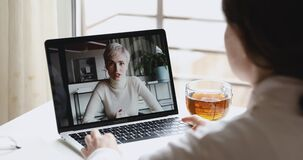 Two young business women distance workers talk in videoconference chat