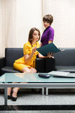 Two young business women with a folder at office. Interior Stock Image