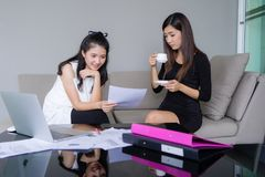 Two young business women happy working together with laptop in office stock photos