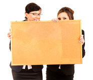 Two young business women holding the cork board Royalty Free Stock Images