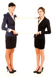 Two young business women holding the whiteboard Royalty Free Stock Images