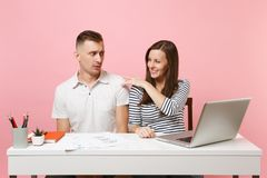 Two smiling business woman man colleagues sit work at white desk with contemporary laptop isolated on pastel pink background. Two young business women men stock images