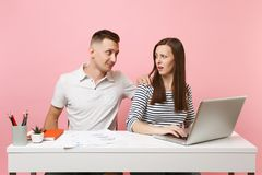 Two smiling business woman man colleagues sit work at white desk with contemporary laptop on pastel pink background. Two young business women men colleagues sit stock photo