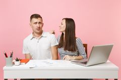 Two smiling business woman man colleagues sit work at white desk with contemporary laptop on pastel pink background. Two young business women men colleagues sit stock image