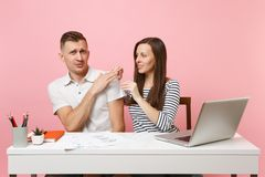 Two smiling business woman man colleagues sit work at white desk with contemporary laptop on pastel pink background. Two young business women men colleagues sit stock photos