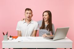 Two smiling business woman man colleagues sit work at white desk with contemporary laptop on pastel pink background. Two young business women men colleagues sit stock photography
