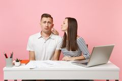 Two smiling business woman man colleagues sit work at white desk with contemporary laptop on pastel pink background. Two young business women men colleagues sit royalty free stock photography