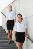 Two young business women posing on stairs Royalty Free Stock Photo