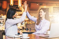 Two young business women sit in cafe at table in front of laptop and make high five. On desk notebook and cup of coffee. Girls celebrate successful transaction Stock Photo