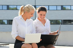 Two young business women sitting with laptop and folder over str Royalty Free Stock Images