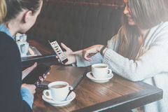 Two young business women sitting at table and using smartphones.Woman showing colleague graphs on smartphone screen. Royalty Free Stock Image