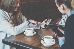 Two young business women sitting at table and using smartphones.Woman showing colleague image on smartphone screen. Stock Photos