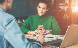 Two young business women sitting at table and working. stock photography