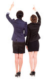 Two young business women standing back and pointing up Royalty Free Stock Image