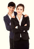Two young business women standing and smiling Royalty Free Stock Photos