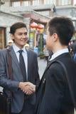 Two young businessman handshaking in houhai, Beijing, China stock photos