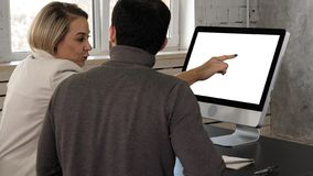 Two young businessman having a meeting at office looking in monitor. White Display. royalty free stock photography