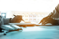 Two young businessman holding pen pointing at the earnings profi Stock Photography