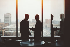 Two young businessman on private meeting. Silhouettes of two young serious successful men entrepreneurs during private meeting discussing something on screen of Royalty Free Stock Photo