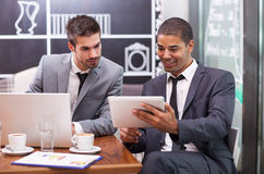 Two young businessman working on a digital tablet in a cafe Royalty Free Stock Photography