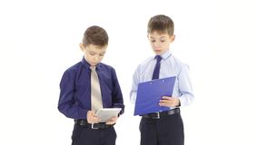 Two young businessmen boys stipulate reports and graphs. White studio. Two young businessmen boys stipulate reports and graphs, one young man holding gray tablet stock footage
