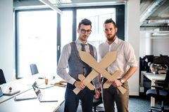 Two young businessmen with swords in an office, having fun. A competition concept. Two young businessmen with cardboard swords in an office, having fun. A royalty free stock photos
