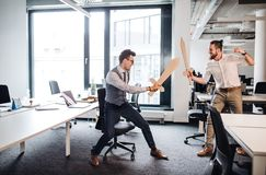 Two young businessmen with swords in an office, having fun. A competition concept. Two young businessmen with cardboard swords in an office, having fun. A stock photography