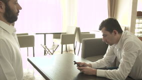 Two young businessmen communicate in a cafe. Manual shooting. HD stock video footage