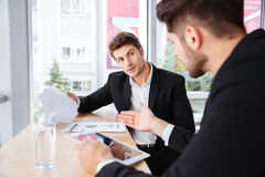 Two young businessmen discussing business plan and using tablet Stock Photography