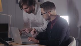 Two young businessmen discussing data in touchpad at meeting. Group of handsome freelancers in modern office with. Image of two young businessmen discussing data stock video footage